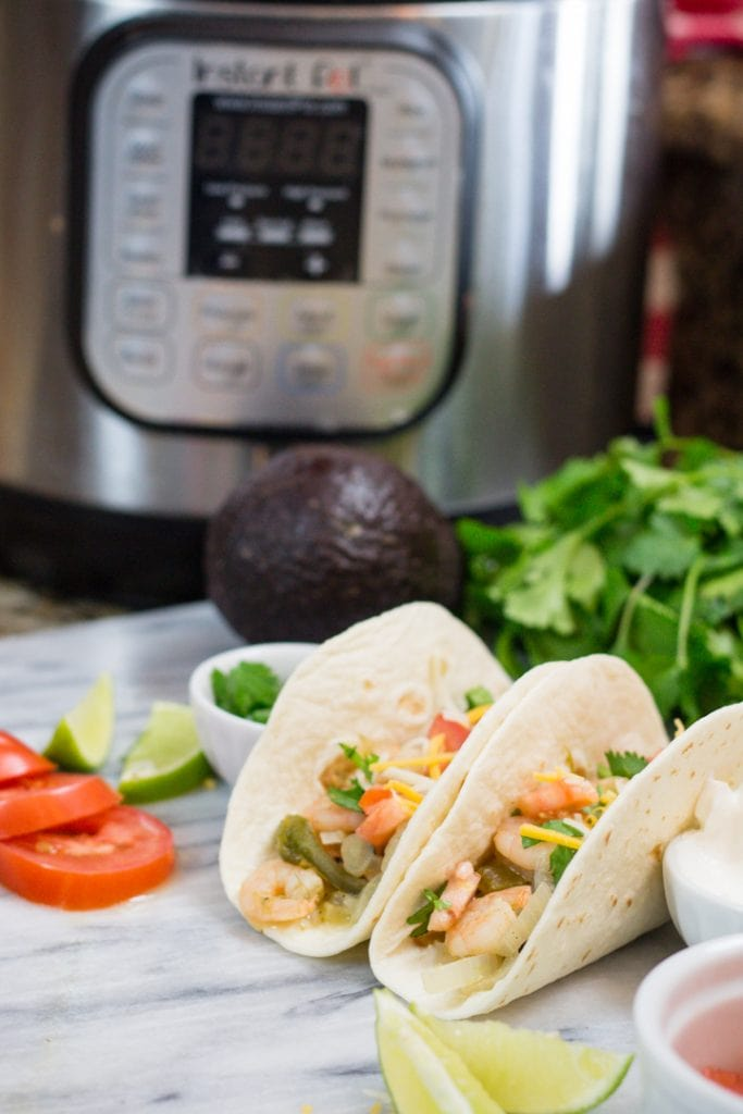 Shrimp Tacos with Cilantro Lime for Taco Tuesday. Shrimp Tacos sitting on cutting board with Instant Pot in background and fresh produce
