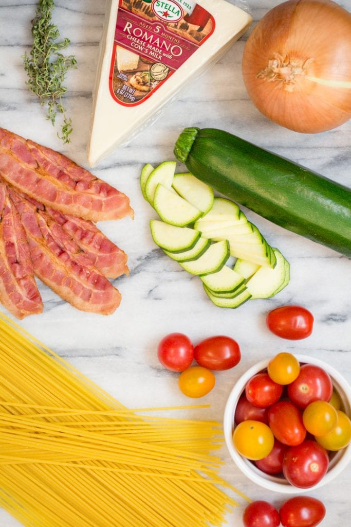 Bacon, Pasta, Zucchini, Cheese, Cheery Tomatoes and Onion Ingredients on a cutting board
