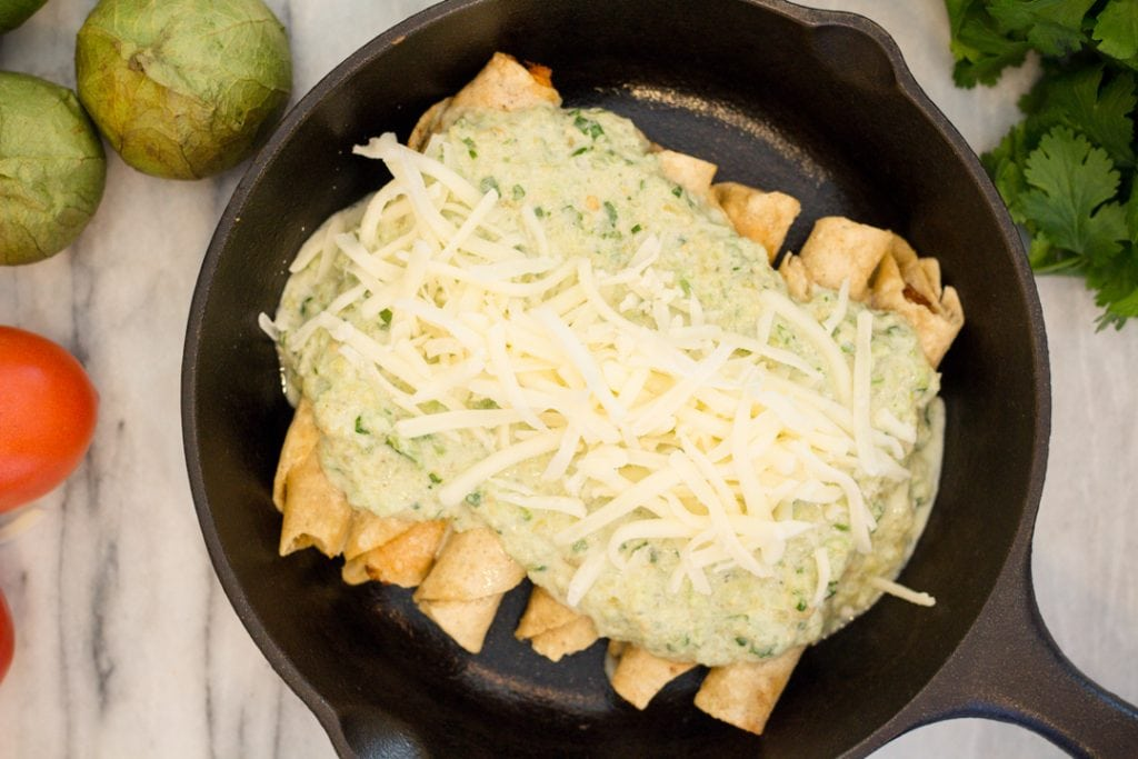Tomatillo Sauce on Chicken Taquitos in a cast iron skillet