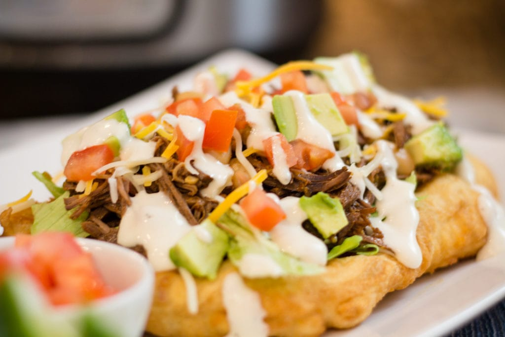 Navajo Taco with Indian Fry Bread, shredded marinated Beef and taco toppings