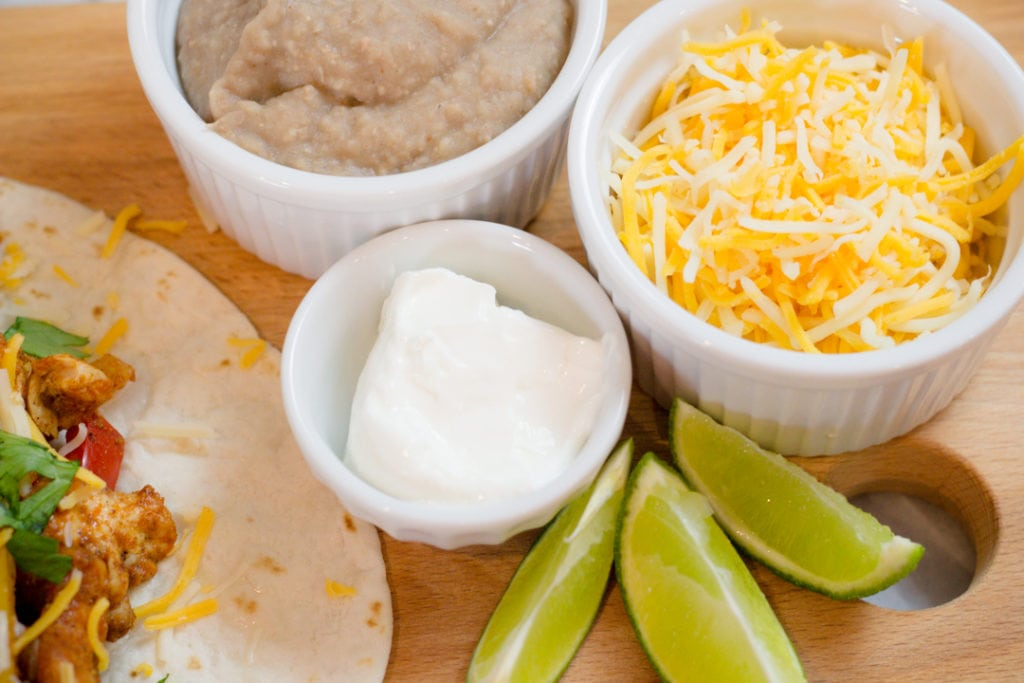 Easy Chicken Fajitas with sour cream, cheese, and beans