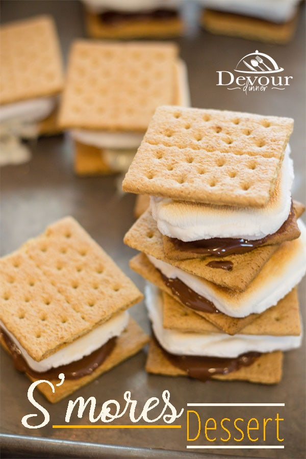 A traditional camping favorite made easy indoors with these Baked S'mores Dessert. Tempt your tastebuds with mini candy bars & make your S'mores Dessert become WOW! I LOVE to roast a marshmallow by the fire. I mean, who doesn't right? #devourdinner #indoorsmore #smoresdessert #smoresdessertrecipe #bakedsmores #marshmallow #dessert #dessertrecipe #easyrecipe #yum #yummy #inmytummy #food #foodie