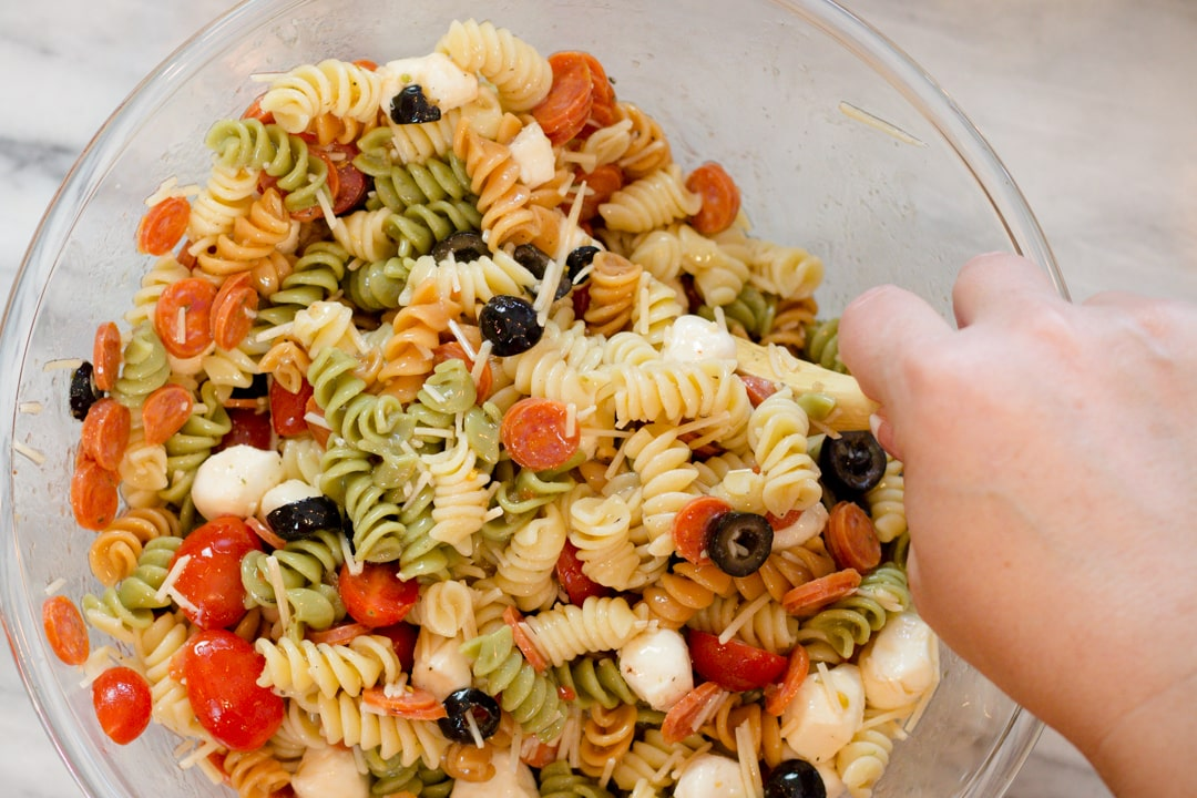 Mixing Pasta Salad with Pepperoni in Bowl