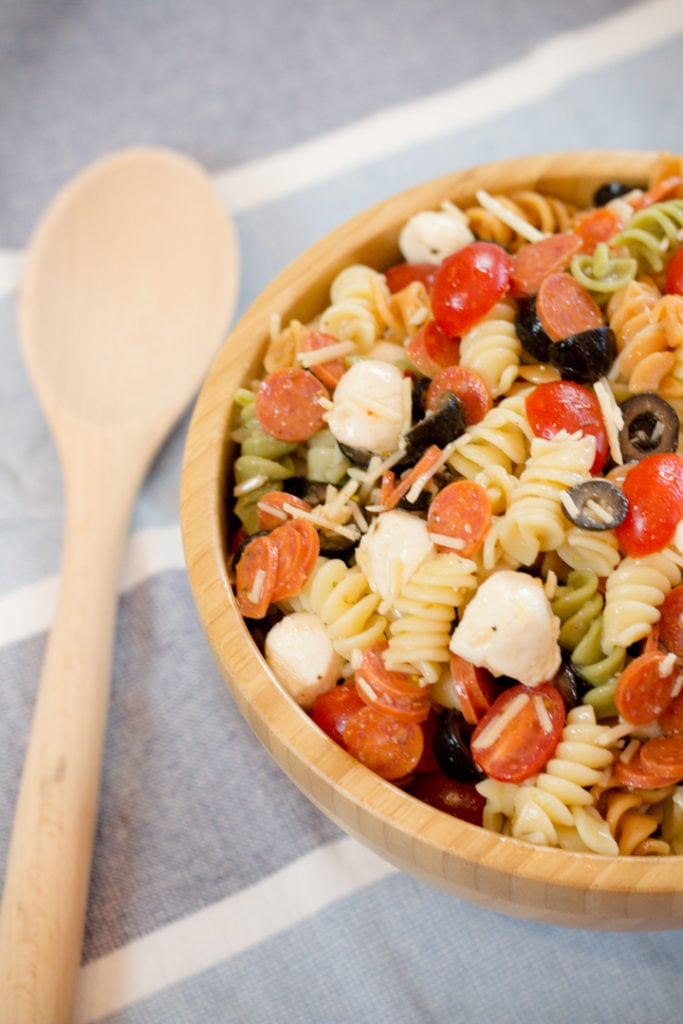Cold Pepperoni Pasta salad with Tri Color Noodles on Blue towel with wooden spoon