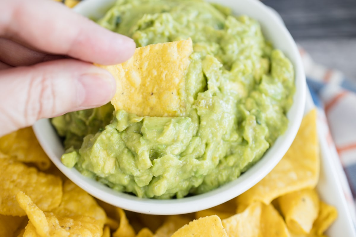 Homemade Guacamole in bowl with chip