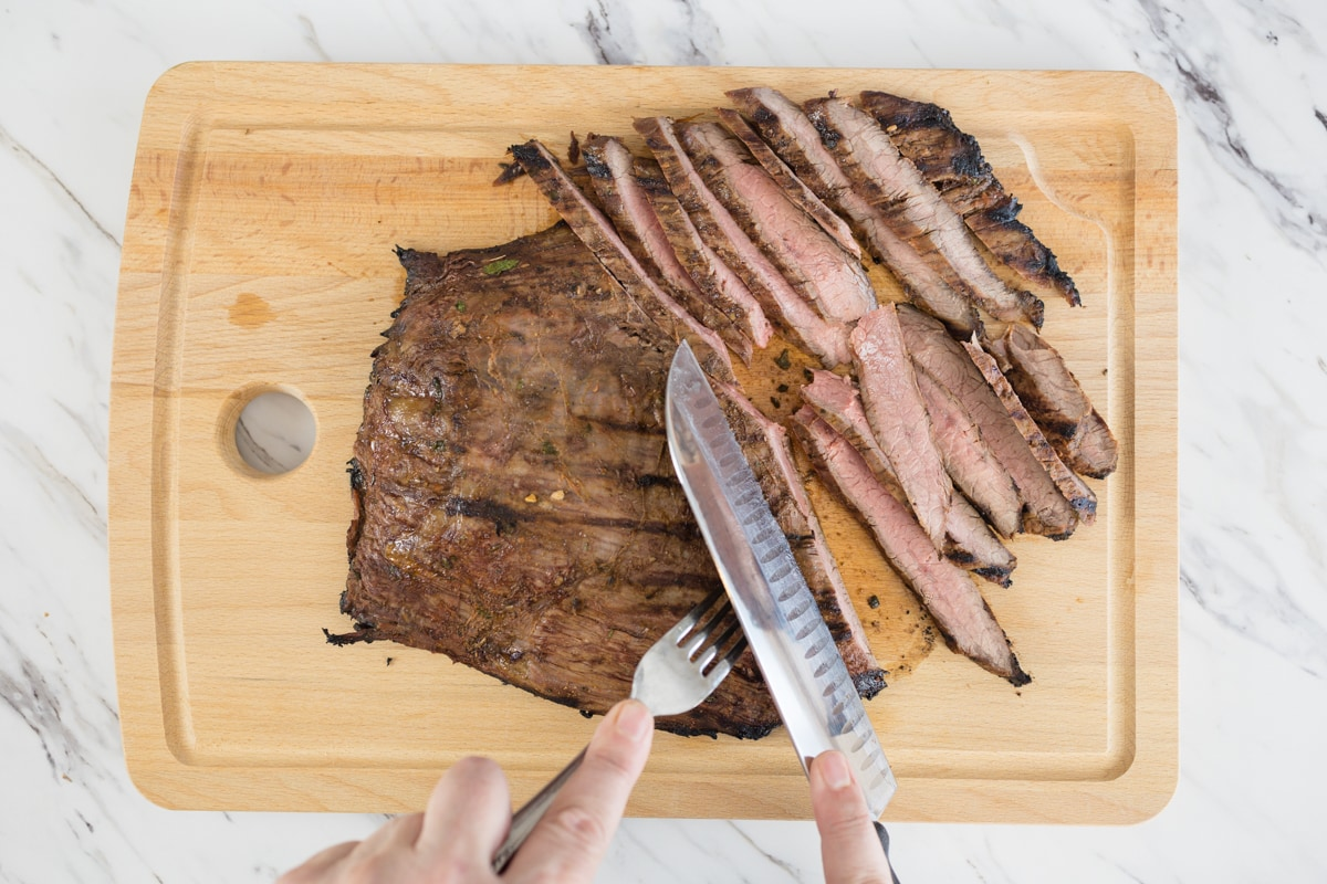 Slice Flank Steak on cutting board