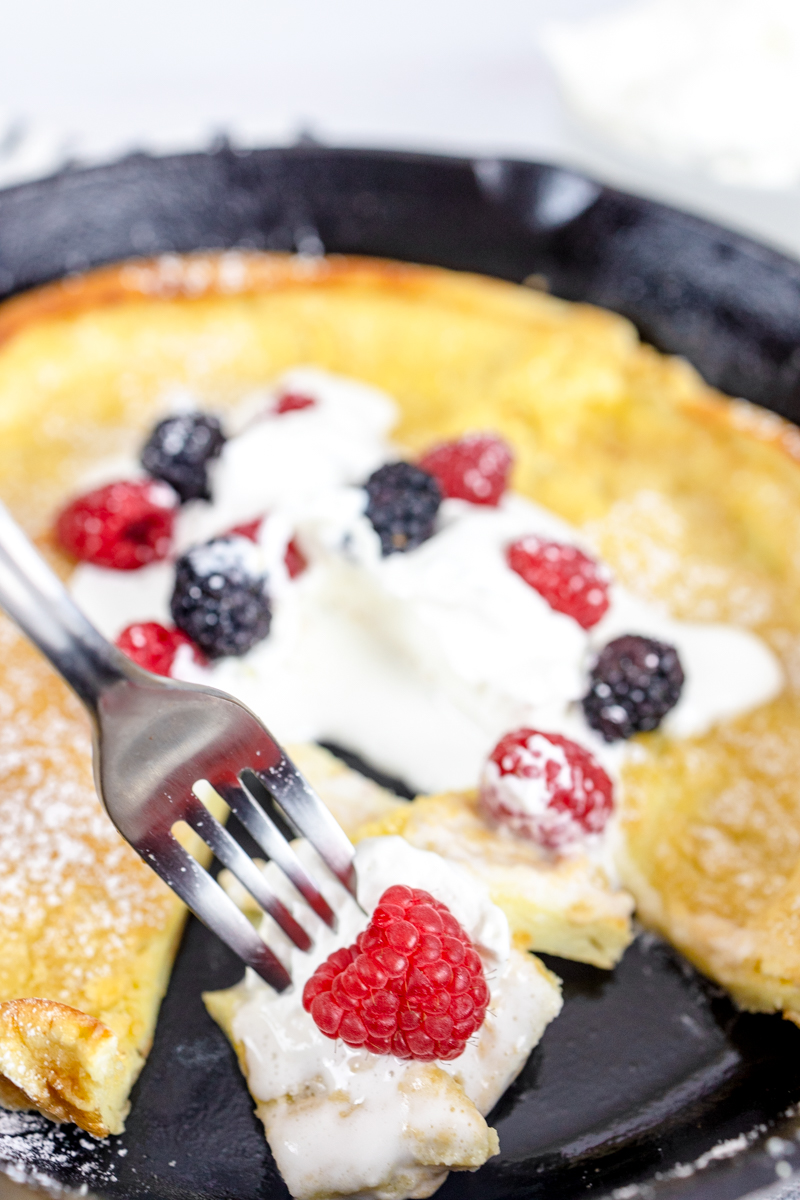 Dutch Baby Pancakes or German Pancakes in Cast Iron Skillet with Cream and Berries