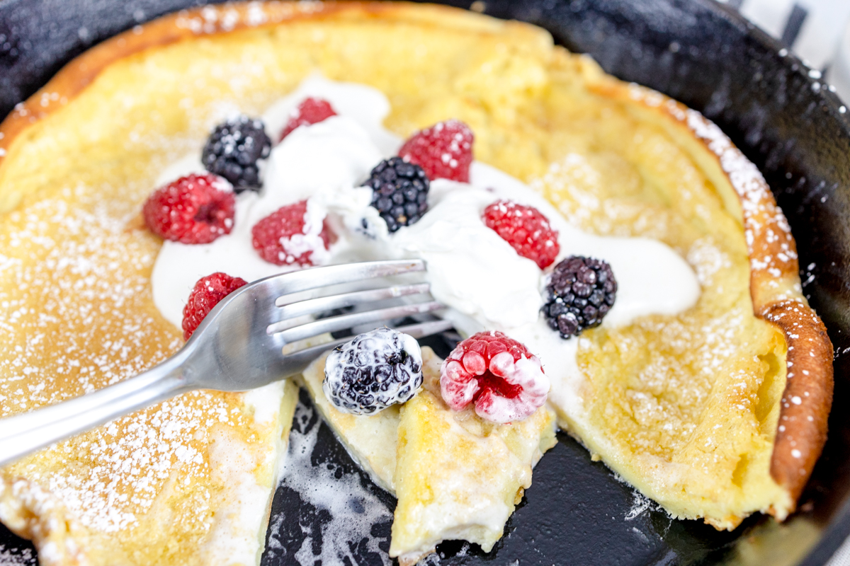 German Pancakes with Whipping Cream and Berries in Cast Iron Skillet