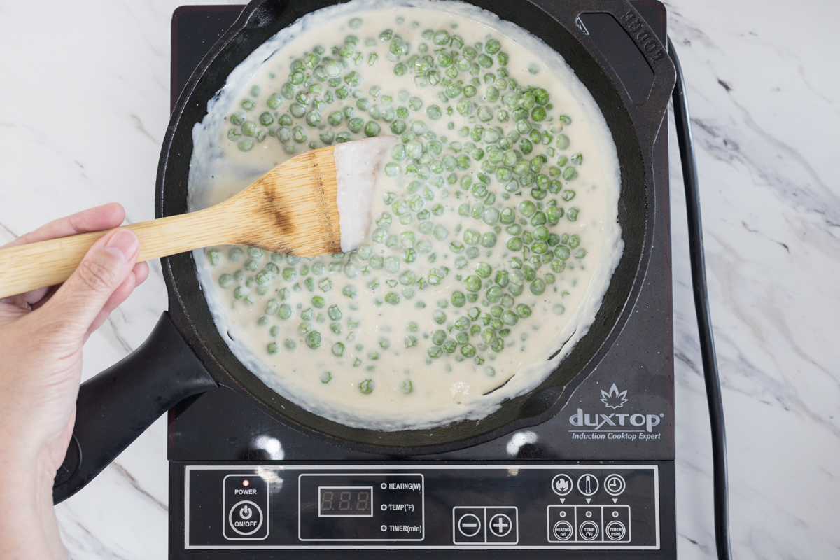 Stir and simmer to combine flavors for Creamed Peas