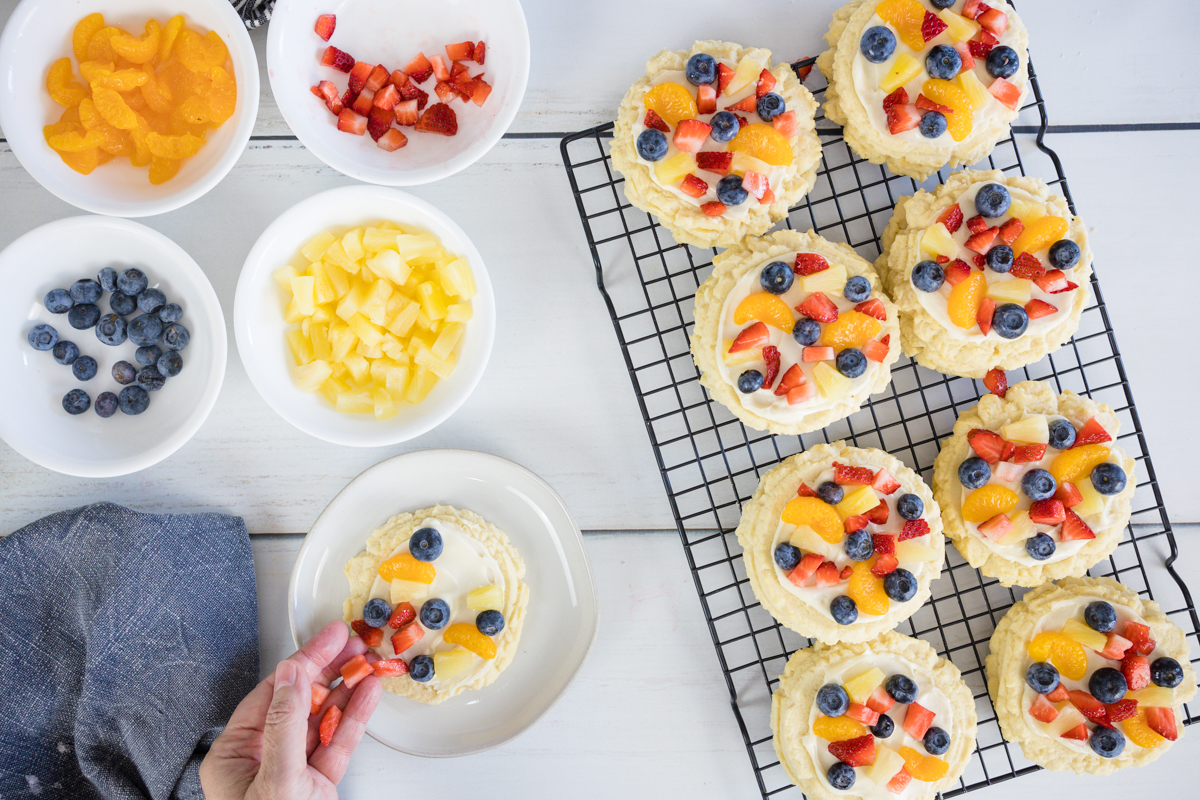 adding fruit to fruit pizza sugar cookies
